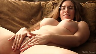 Nerdy girl lies down on the bed to play with her large vibrator